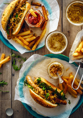 Delicious fresh hot dogs in homemade buns with arugula and ketchup, with beer and French fries on a wooden background.