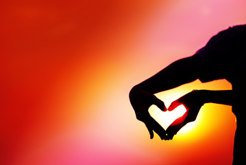 "Silhouette of two hands make ""heart symbol"" with multi-color construction work sunlight background,Love and Valentines concept,vivid color"