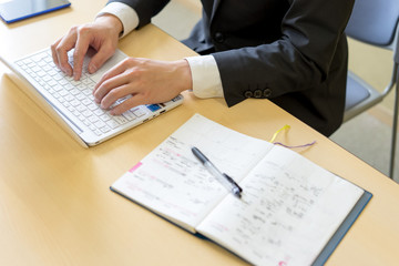 スケジュール帳を開いてパソコンを打つ就活生のイメージ