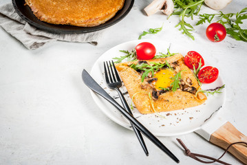 French cuisine. Breakfast, lunch, snacks. Vegan food. Traditional dish galette sarrasin. Crepes with eggs, cheese, fried mushrooms, arugula leaves and tomatoes. On a white concrete table. Copy space