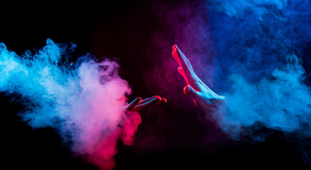 hands reaching from colorful smoke on black background