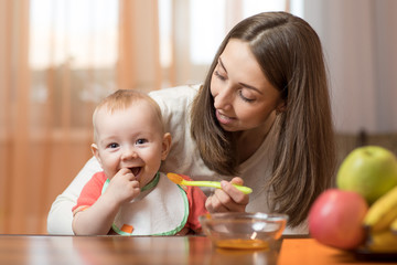 Young mother feeding baby son with fruit puree