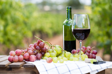 glass of red wine and ripe grapes on table