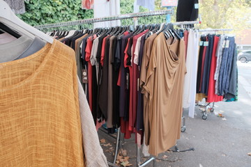 Second hand clothes hanging on a market stall