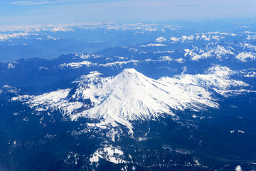 Snowcapped Mount Rainier and the Cascade Rangeas seen from an airplane window