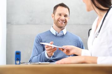 Pacjent w gabinecie lekarskim. Lekarz podaje receptę pacjentowi.