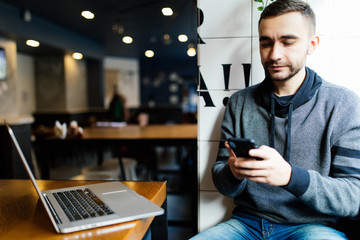 Prosperous male entrepreneur sending message and multimedia files on smartphone working in cafe. Experienced marketing manager synchronizing phone data with laptop share photos for project