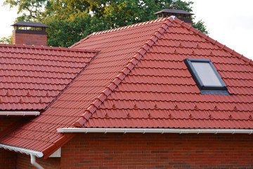 New Red Shingles Roof with Skylights Windows and Rain Gutter. New brick house with chimney