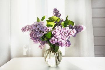 A bouquet of fresh lilacs in a beautiful glass vase on a white table in a farmhouse.
