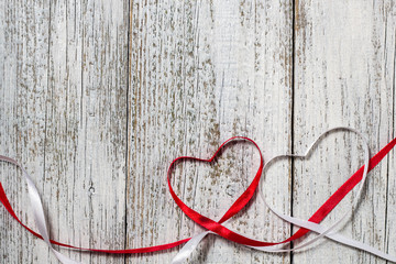 Red and white ribbon hearts for valentines day on wooden background