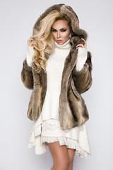 Beautiful, sexy blond model wearing a dress and elegant fur coat