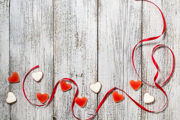 Marmalade candy shape heart and red ribbon on wooden table, valentine day composition, greeting card