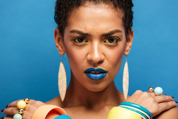 Colorful photo of strict serious mixed-race woman with trendy makeup and accessories posing with crossed hands on shoulders, over blue wall