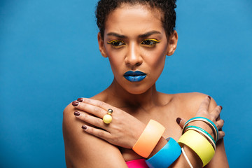 Colorful photo of tense or disappointed mixed-race woman with trendy makeup and accessories posing with crossed hands on chest, over blue wall