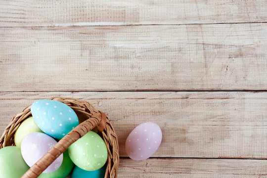 Colorful easter eggs in basket on wooden background. Easter holiday. Space for text.
