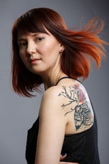 Photo of woman with tattoo on back on empty gray background
