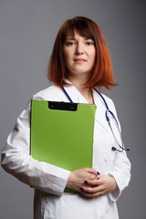 Picture of young female doctor with phonendoscope and green folder in hand