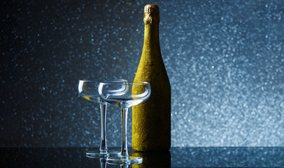 Picture of bottle of champagne in gold wrapper with empty wine glass on gray background