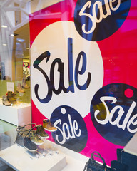 big letters indicate sale in shop windows of shoe store