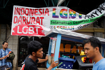 A street vendor walks past a banner reading 'Indonesia LGBT Emergency' in front a mosque in Jakarta
