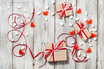 Valentines Day candy hearts marshmallows and box of gifts in craft paper over white wooden background