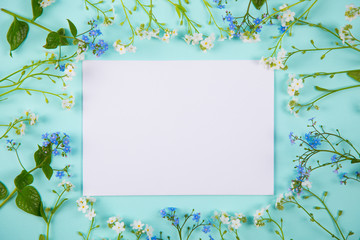 Clear sheet of white paper surrounded with blue and white little flowers on light mint background.