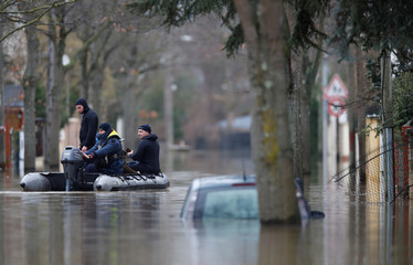 Paris police divers use a small boat to patrol a flooded street of a residential area in Villeneuve-Saint-Georges