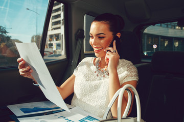 Young businesswoman talking on the phone in the back seat of the car