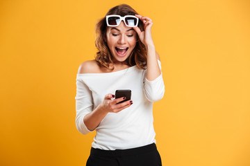Excited young woman using mobile phone.