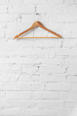one brown wooden hanger on white wall