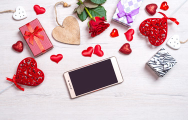 Wooden white background with hearts, gifts, red rose and smartphone. The concept of Valentine Day