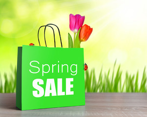 Green shopping bag with spring sale word and tulip flower on table.