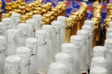 Big amount of golden and white champagne bottles necks and top caps at standing the light background.