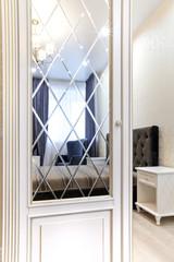 Гардеробный шкаф в спальне с зеркалом гладким и с фацетом. Интерьер с контрастом светлого и темного