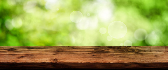 Green bokeh background with wooden table