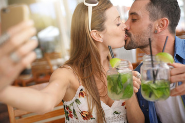 Couple taking selfie pictures while drinking mojitos