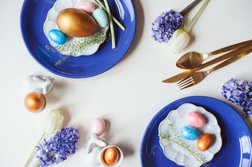 Easter holiday greeting card, dining table with plate, golden cutlery, painted eggs and hyacinth flower on white background with copy space. Flat lay, top view, trendy modern celebration style
