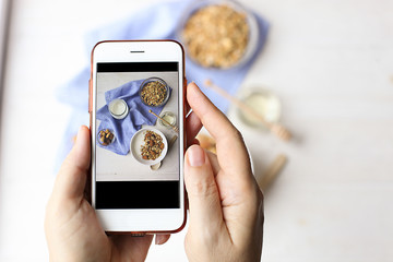 Close up of female hands holding mobile phone taking a picture of granola cereals, milk yogurt and trail mix vegetarian dieting breakfast for a new food blog article. Top view, overhead, copy space.