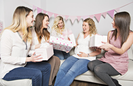 Best Friends on baby shower party celebrating giving kid stuff as present