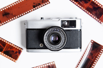 Vintage film camera and negatives on a white background