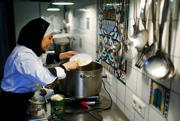 Syrian migrant Jazmati cooks in a kitchen of an Cafe in Berlin