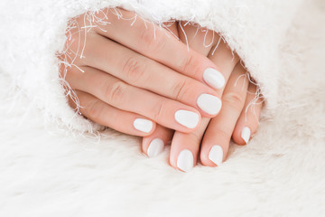 Elegant groomed woman's hands with white nails on the fluffy mat. Cares about clean, beautiful, soft hands skin and nails in winter time. Manicure beauty salon. Healthcare concept.