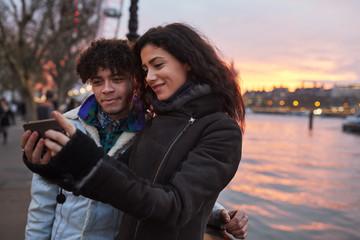 Couple Taking Selfie During Walk Along South Bank In London