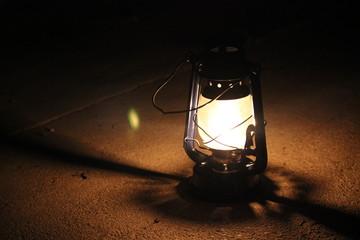 Kerosene lamp lights in a dark near a stone wall.