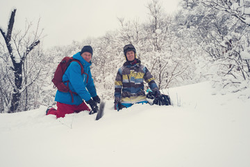 Happy snowboarders are sitting in deep snow after freeride