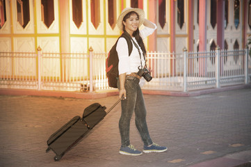 Pretty Asian traveler female with luggage and waiting train at railway station in Thailand.