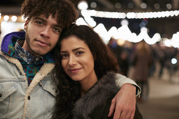 Portrait Of Young Friends Enjoying Christmas Market At Night
