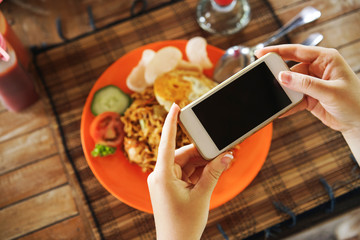food blogger girl takes a picture of Asian food on her smartphone.