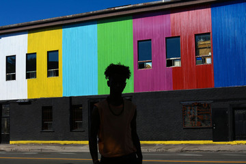 Man Standing Near Colorful Building