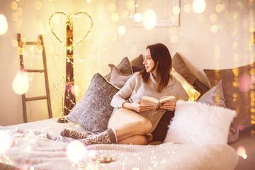 schöne Frau zu hause im Bett beim lesen